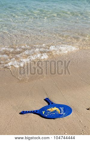 Racquets On A Wet Sandy Beach With Map Of Greece On Them.
