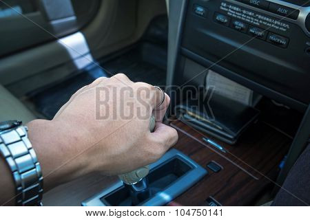 Hand of driver shifting gear of automatic car