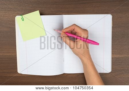 Womans writing hand on table