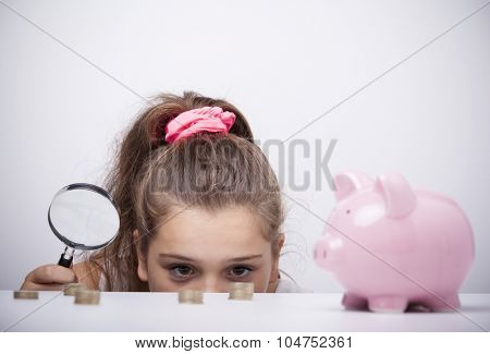 Little girl holding a magnifying glass and looking to the savings