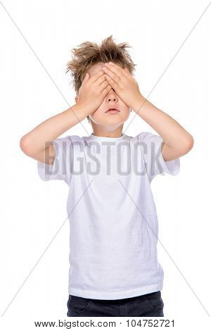 A boy in white t-shirt closed his eyes with his hands. Isolated over white background.