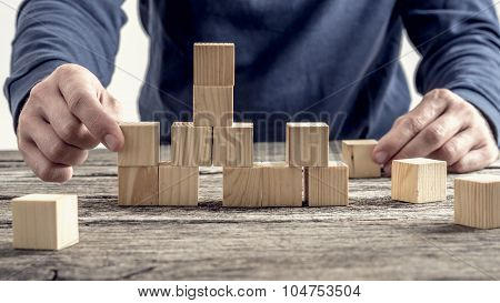 Man In Blue Shirt Arranging Wooden Blocks On Rustic Table