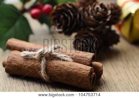 Cinnamon Sticks Bundle, Holly And Fir Cones On Oak Table