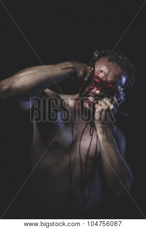 Rage, naked man with blindfold soaked in blood