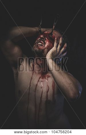 Sinister, naked man with blindfold soaked in blood