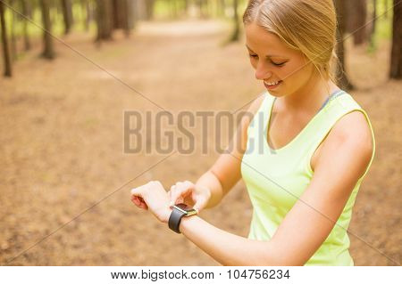 Woman monitoring her pulse on smartwatch