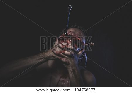 Massacre, naked man with blindfold and forks