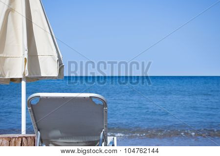 White Sunbed And White Closed Parasol Infront Of Blue Sky And Sea Horizon.