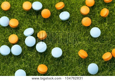 Orange and blue pills spilling on the green grass