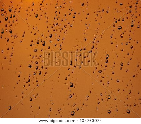Rain drops on a glass in sunset hours
