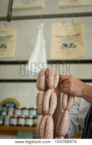 Butcher Holding A String Of Sausages