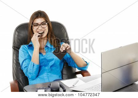 Young Beautiful Businesswoman Eating Chocolate At Her Workplace In Office