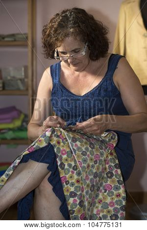 Middle Aged Woman Sewing With Needle And Thimble