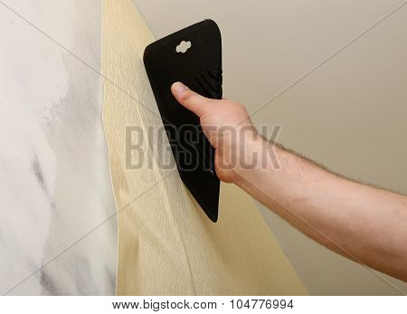 Worker putting up wallpaper with spatula