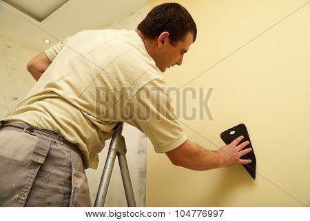 Worker glues new wallpaper