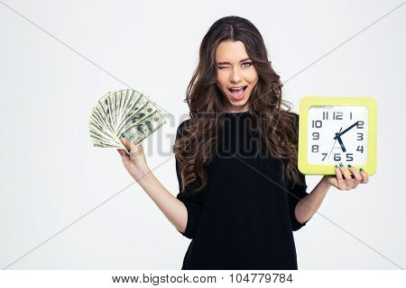 Portrait of a happy girl holding wall clock with bills of dollar and winking at camera isolated on a white background