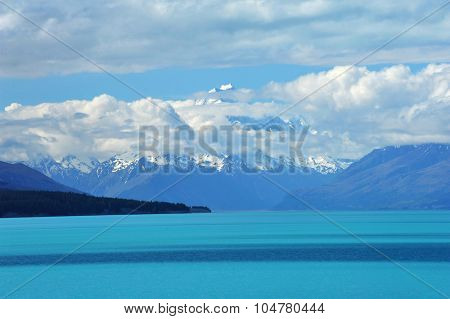 Mighty Mt. Cook is appearing from the clouds near the incredibly blue lake Pukaki at New Zealand