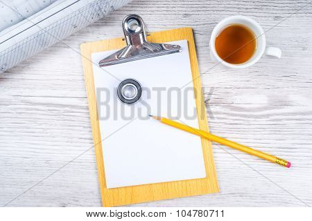 Red Safety Helmet Hat And Clipboard And Drawing Tools On Wood Background