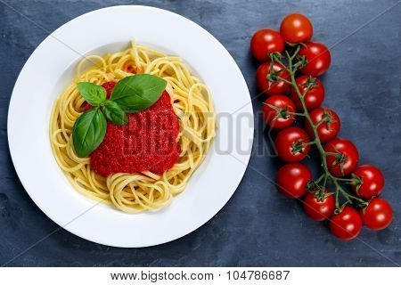 Spaghetti With Marinara Sauce And Basil Leaves On Top, Decorated With Cherry Tomatoes. On Blue Backg