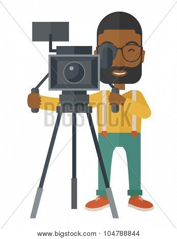 An african-american cameraman with beard and glasses looking through movie camera on a tripod vector flat design illustration isolated on white background. Vertical layout.