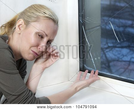 The housewife cries bad quality window has burst because of cold weather