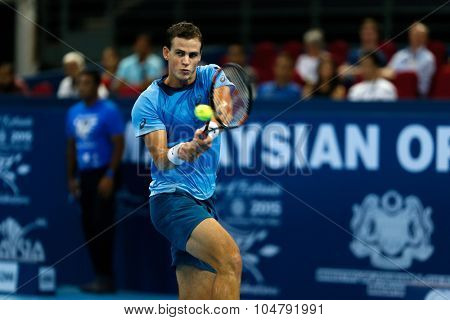 KUALA LUMPUR, MALAYSIA - OCTOBER 02, 2015: Canada's Vasek Pospisil plays a backhand return in his match at the Malaysian Open 2015 tennis tournament held at the Putra Stadium, Malaysia.