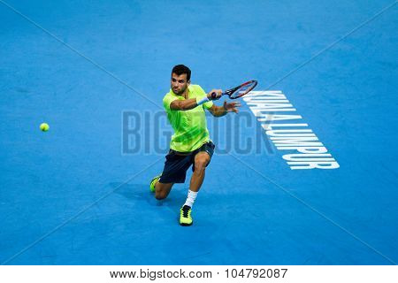 KUALA LUMPUR, MALAYSIA - OCTOBER 02, 2015: Grigor Dimitrov of Bulgaria hits a backhand return in his match at the Malaysian Open 2015 tennis tournament held at the Putra Stadium, Malaysia.