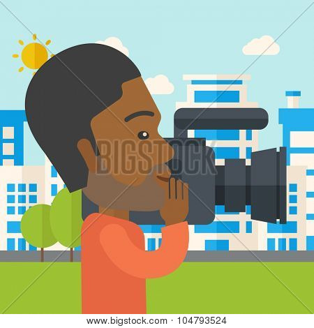 An African American hipster cameraman with video camera taking a video with buildings around vector flat design illustration. Square layout.