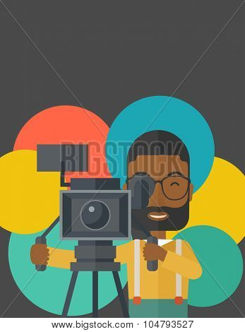 An African American cameraman with beard and glasses looking through movie camera on a tripod vector flat design illustration. Vertical layout with a text space.