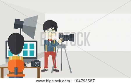 An Asian photographer stands with camera while another man sits in front of monitor in studio vector flat design illustration. Horizontal layout with a text space.