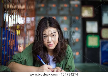 Charming Asian Girl Sitting By Wooden Table And Reading Book