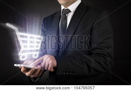 Businessman with shopping cart on smart phone
