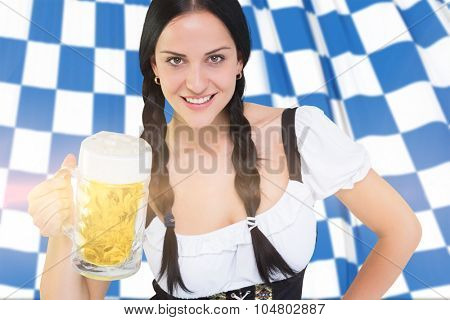 Pretty oktoberfest girl holding beer tankard against blue and white flag