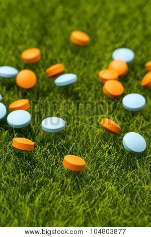 Orange and blue round pills spilling on the green grass