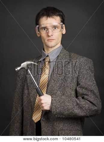 Man In Goggles Keeps In Readiness A Hammer
