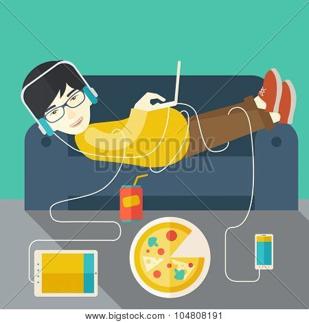 An asian man in glasses and headphones lying on a sofa with electronic devices and fast food vector flat design illustration. Square layout.