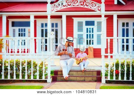 Father And Son Playing Music, Sitting On Stairs