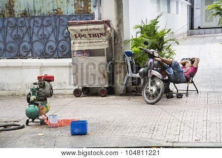 Man Rests On Scooter On Street Of Ho Chi Minh City, Vietnam