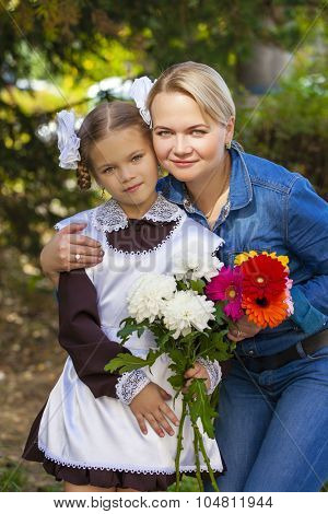 Close up portrait of a beautiful nine year old little girl and happy mother in autumn park