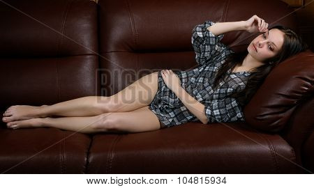 The Thoughtful Girl Lies On A Leather Sofa
