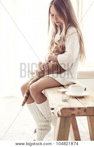Preteen girl wearing warm knitted clothing is sitting on rustic bench with her cat in white living room. Winter weekend.
