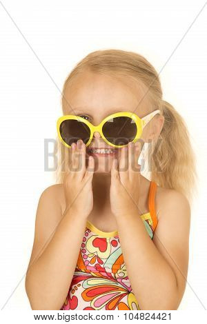 Silly Blond Girl Smiling Putting On Her Sunglasses