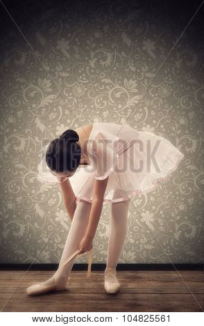 Young Ballerina While Tying Ballet Shoes