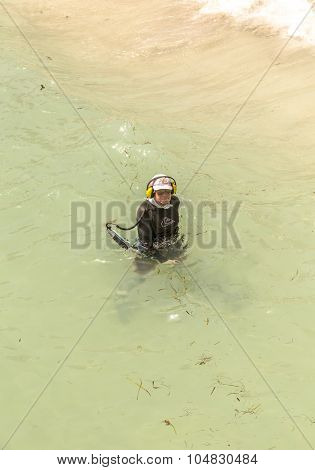 Man Searches With Metal Detector  For Treasuries In The Ocean