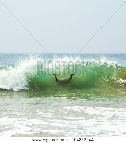 Swimmer in a funny upside-down pose dives under the sea foamy waves of the Arabian Sea on the sunny