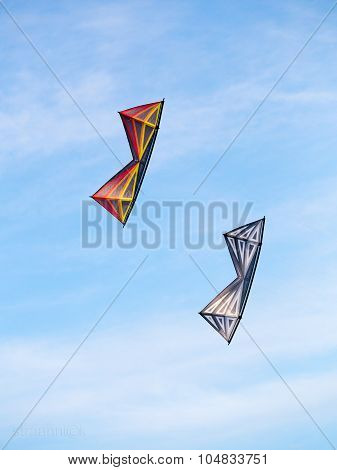 The pair of stunt kites perform aerobatics in the blue sunny summer sky at the kite festival