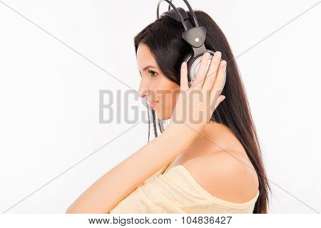 Pretty Girl Listening To Music On Headphones Standing In Half-face