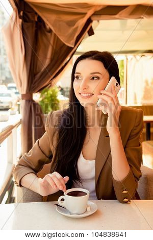 Young Cherful Woman Talking On Phone At Dinner With Cup Of Coffee