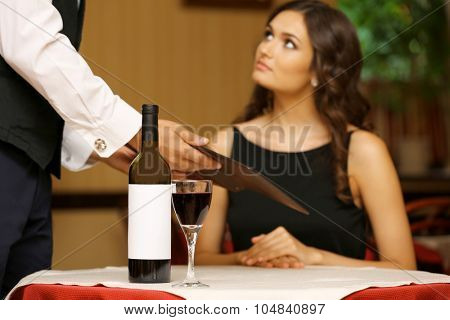 Young pretty lady at the restaurant. Waiter takes menu