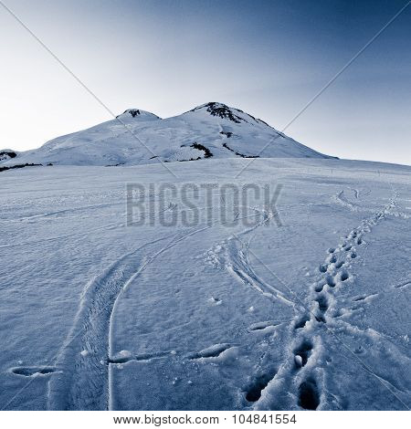 Footprints in the snow at the foot of a mountain peak Mount Elbrus